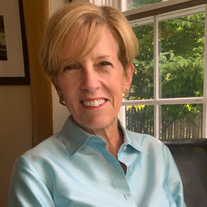 headshot of blog author Christie Peck, sitting near a window with a bright blue shirt on, lightly colored skin, and a short haircut with sandy brown hair