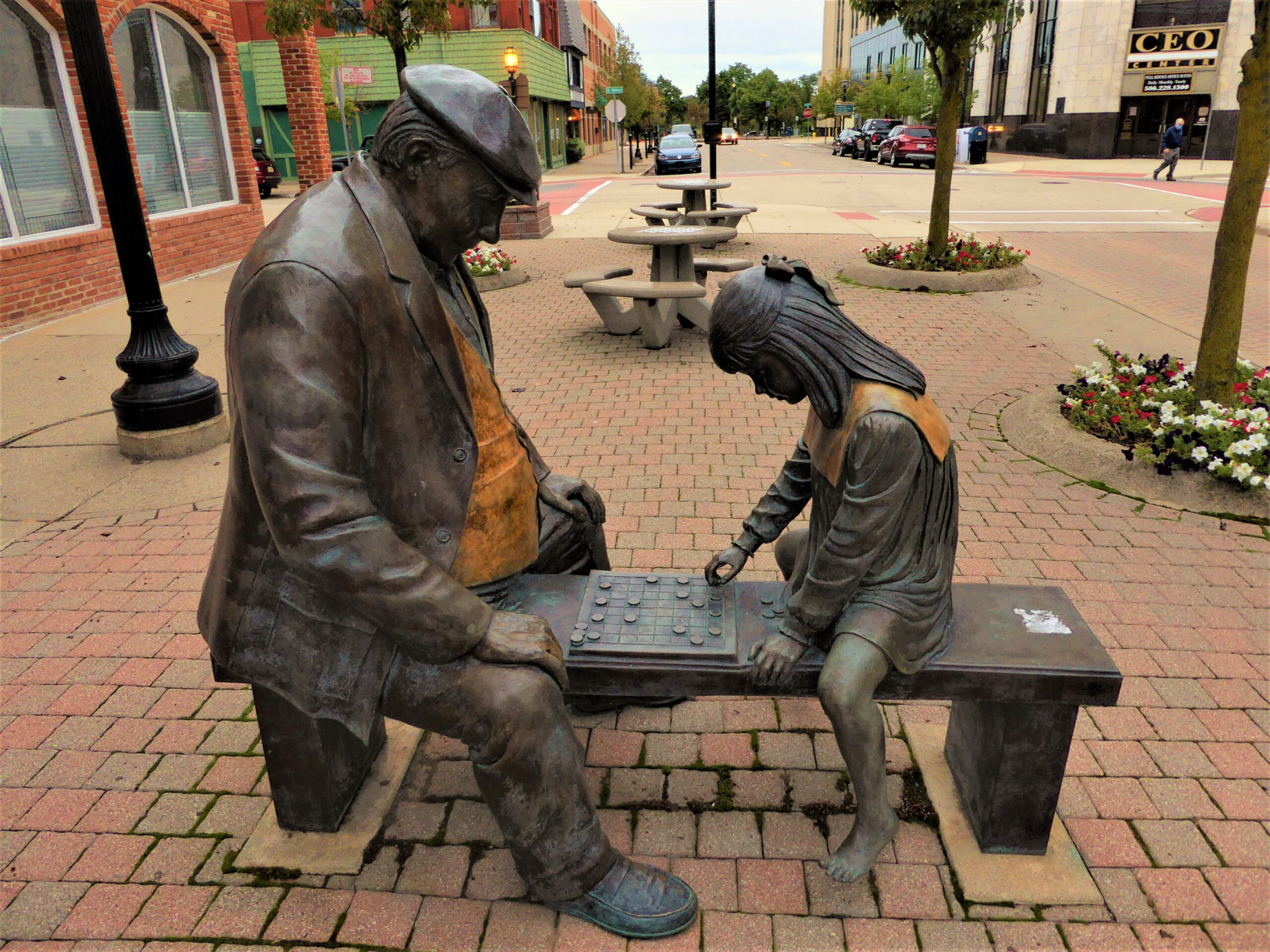 Photo of a sculpture of an older man playing checkers with a young girl, both are sitting on a bench.