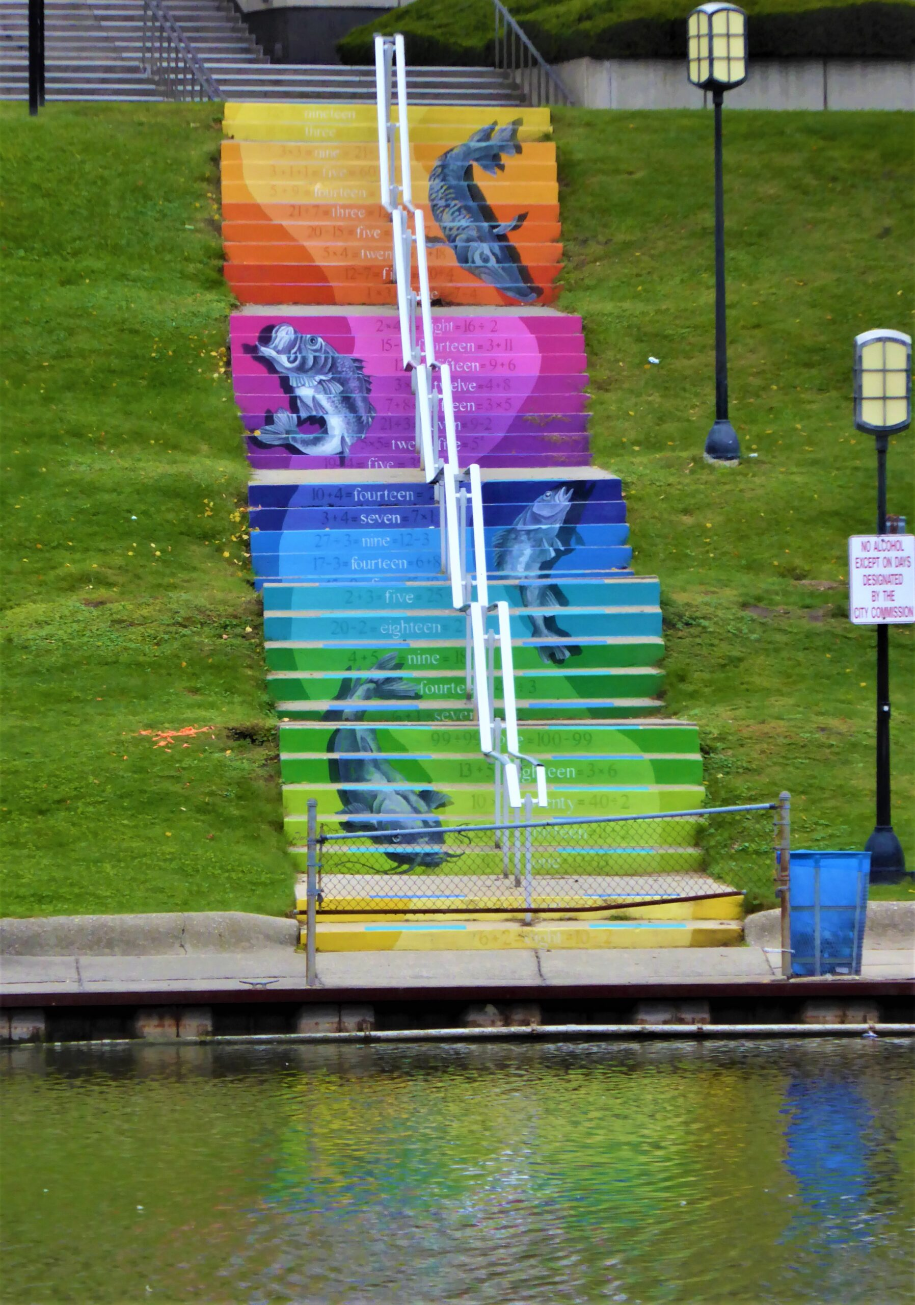 A photo of a mural on stairs that is a rainbow with a few fish jumping painted on top