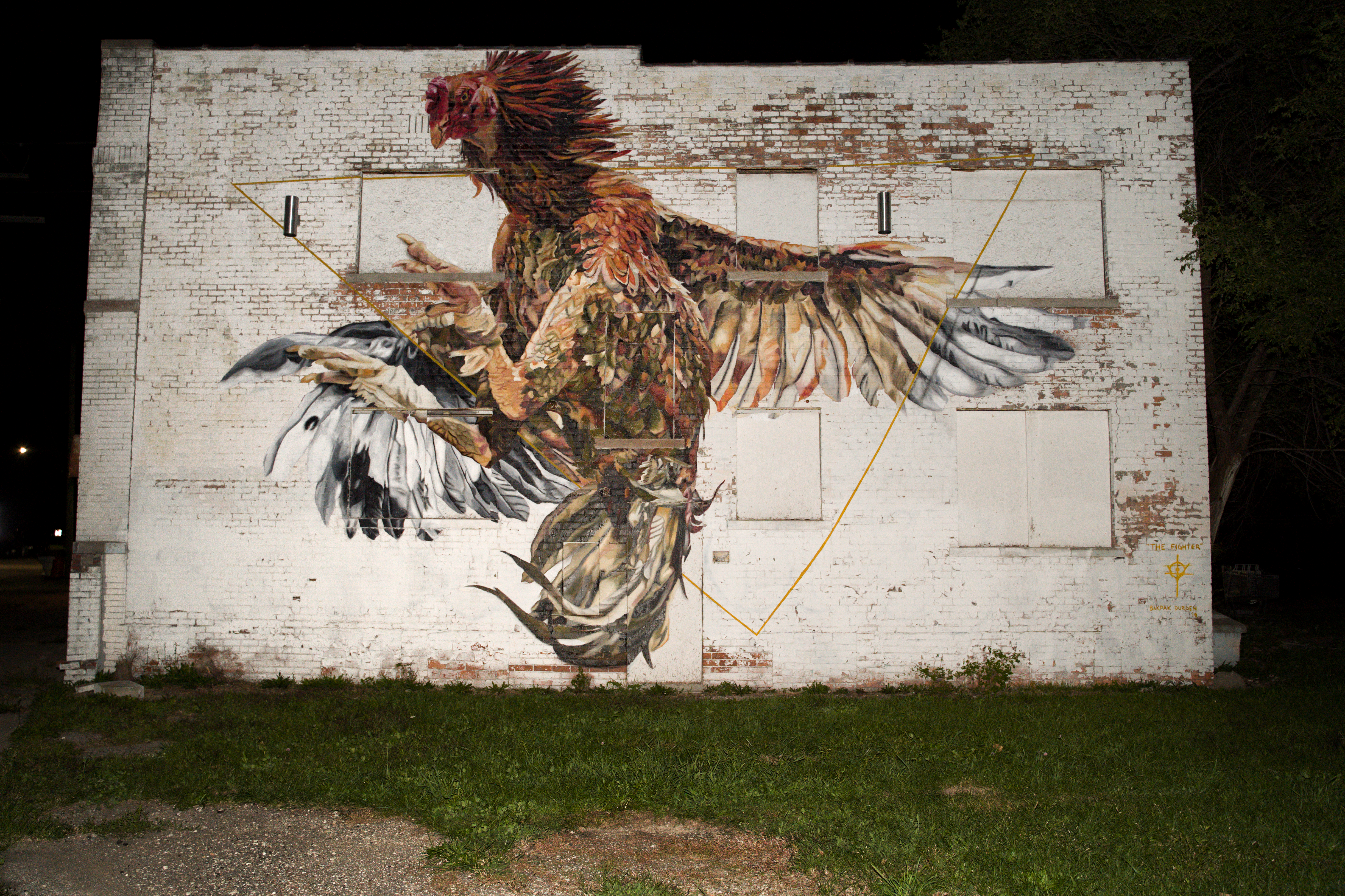 Photo of a mural of a rooster with its wings extended and its talons in the air launching towards the viewer.