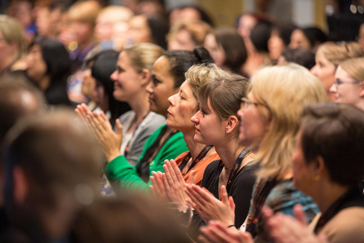 An audience of women applauding