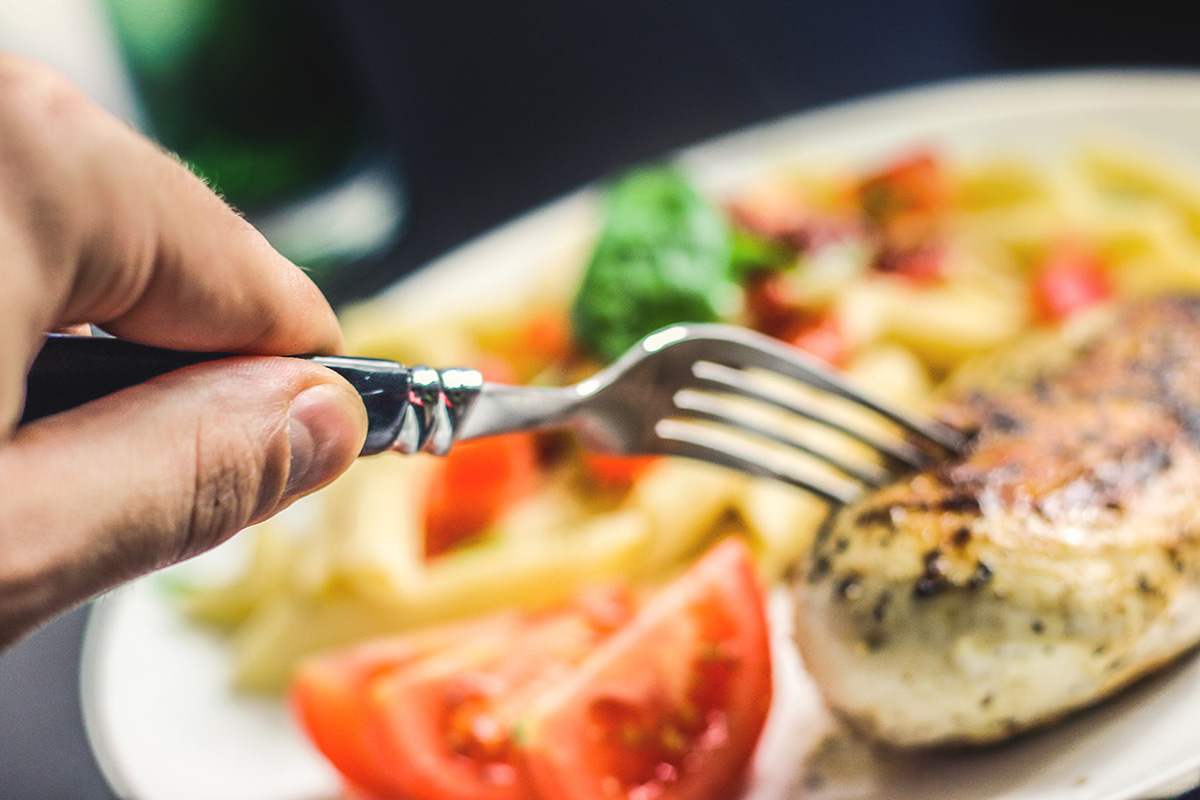 A fork being stuck into a chicken breast on a plate of healthy food