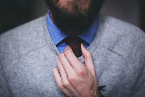 Close-up of a man adjusting a necktie