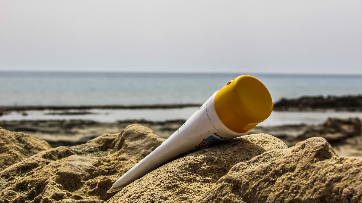 A bottle of sunscreen in a pile of sand on a beach