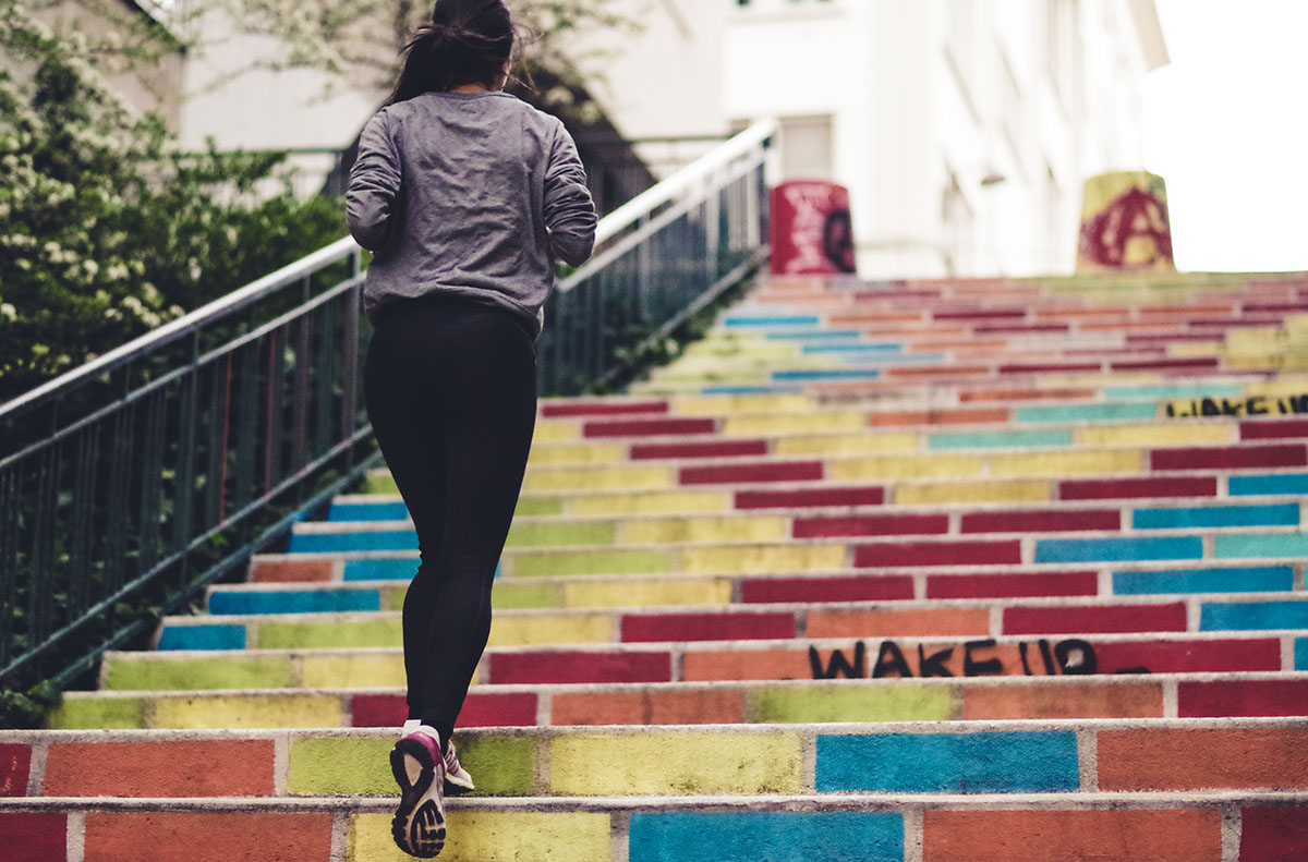 A woman running up outdoor stairs in athletic clothing