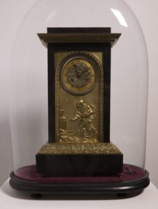 Neoclassical figural mantel clock with chimes: bronze dore and wood clock displayed under a hand-blown glass bell and resting on a padded wood pedestal 20 x 16 x 10 in.