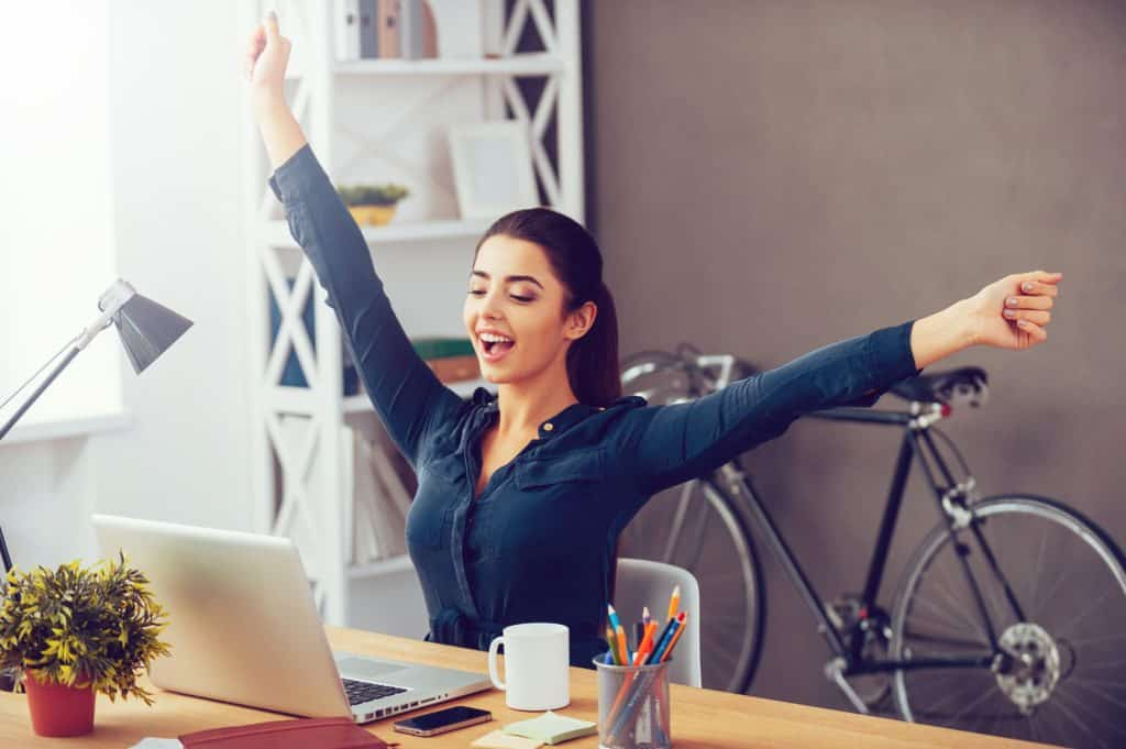 Attractive young woman stretching out hands and looking excited while sitting at her working place and looking at laptop