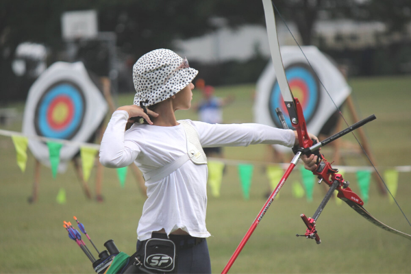 Young female archery shooting
