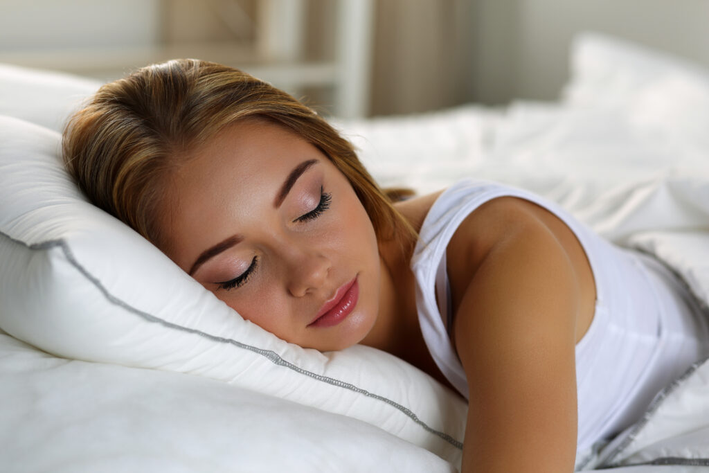 Young beautiful blonde woman portrait lying in bed sleeping
