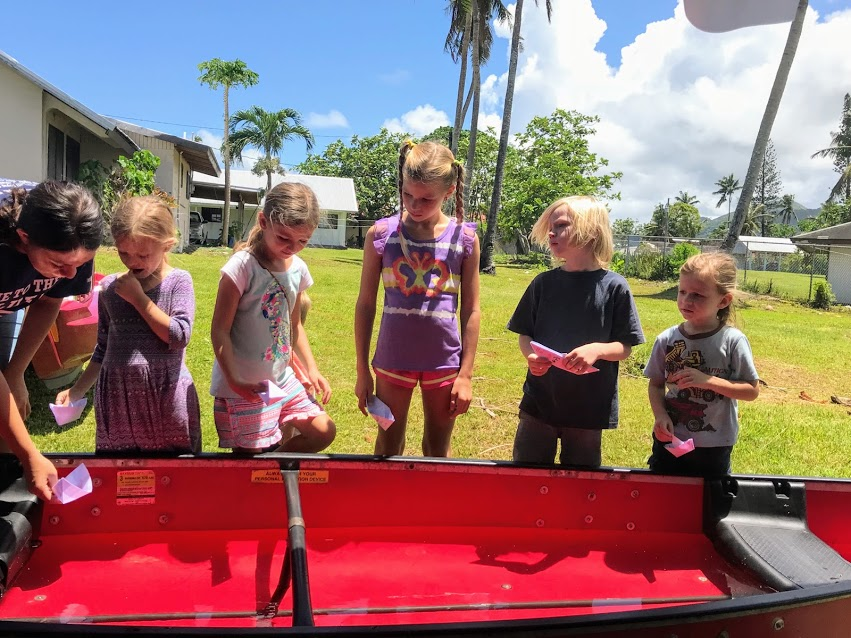 Kids racing origami paper boats for Flag Day