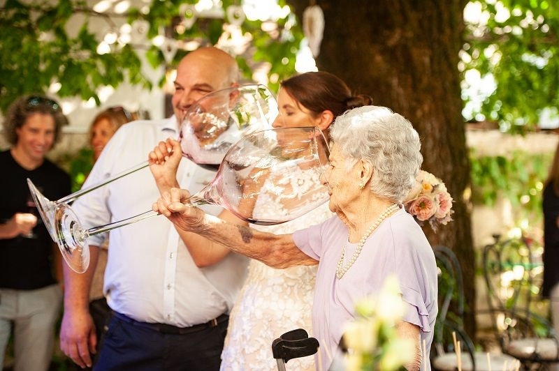 Bride-and-Her-Mother-in-Law-Drinking-Wine-From-Large-Wineglass-at-Wedding-Celebration-cm