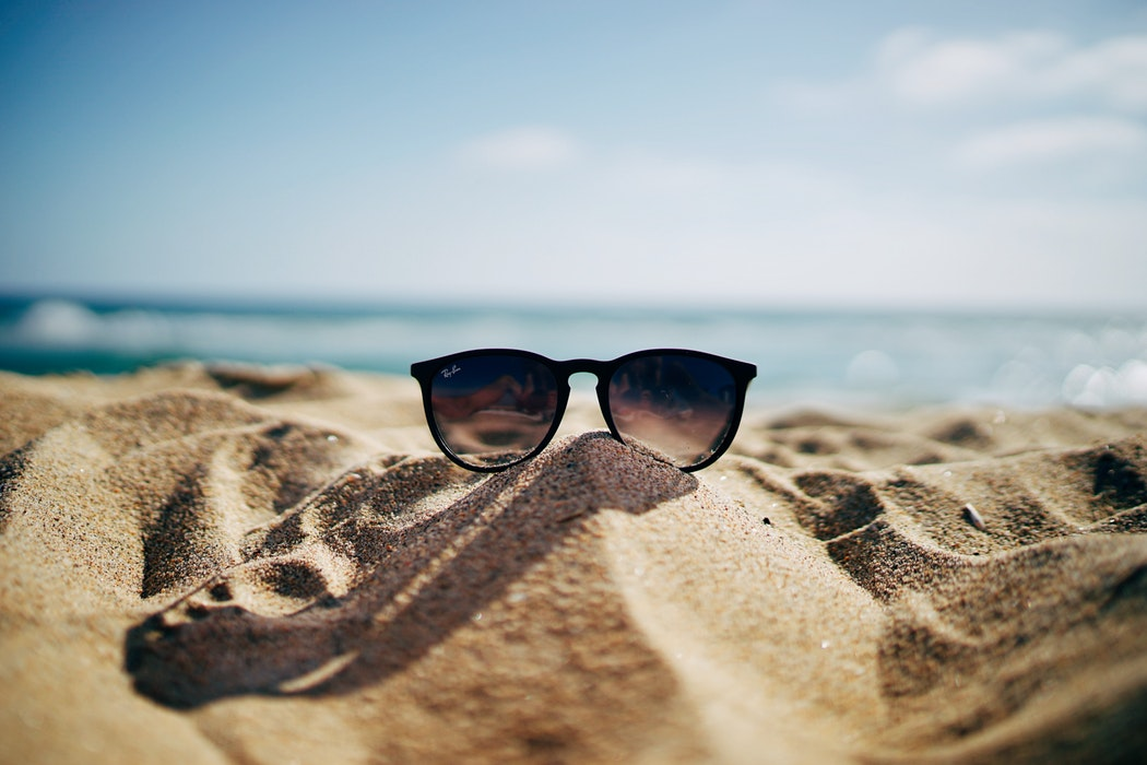 Sunglasses on a pile of sand at the beach.