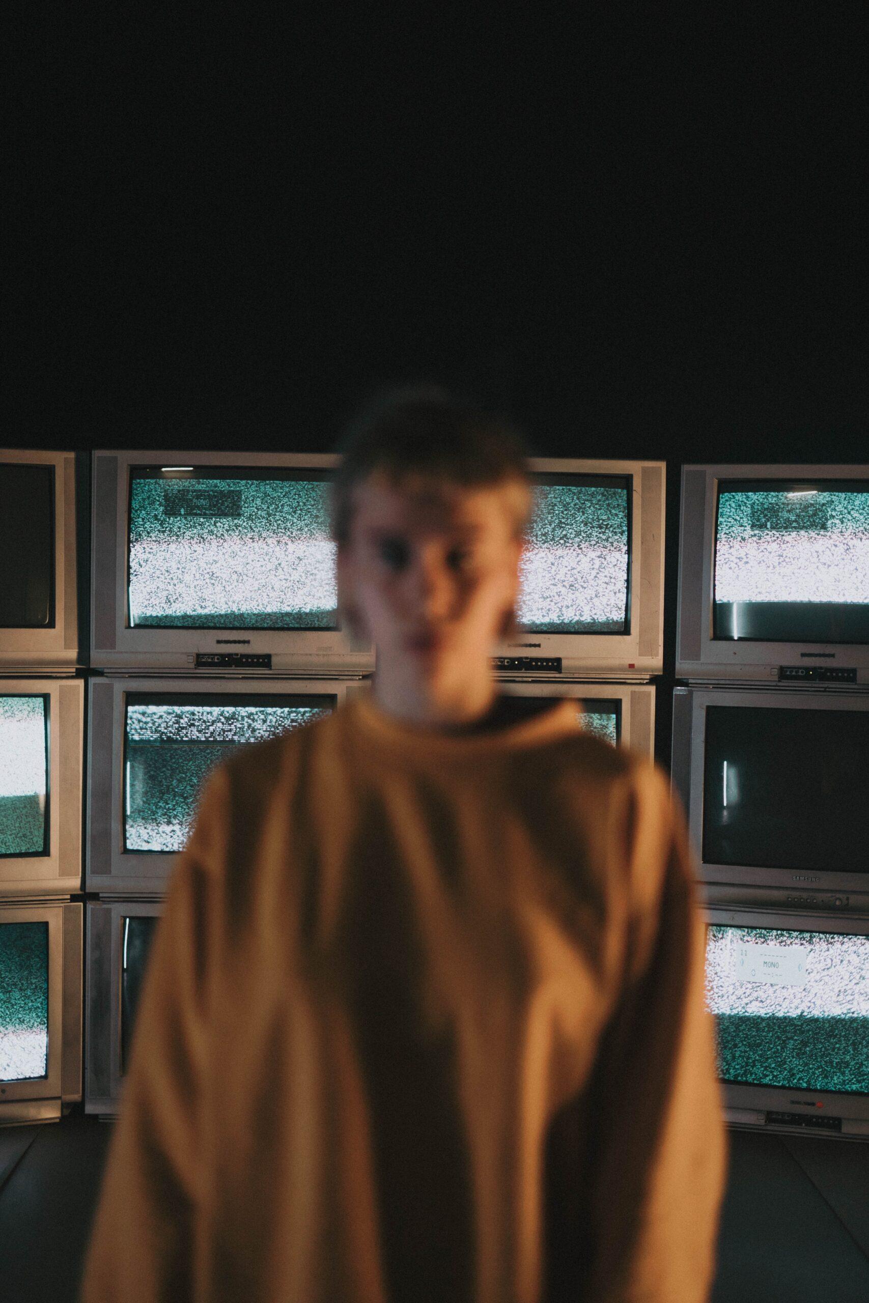 man in brown sweater standing near window