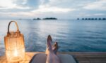 person lying on chair and facing on body of water