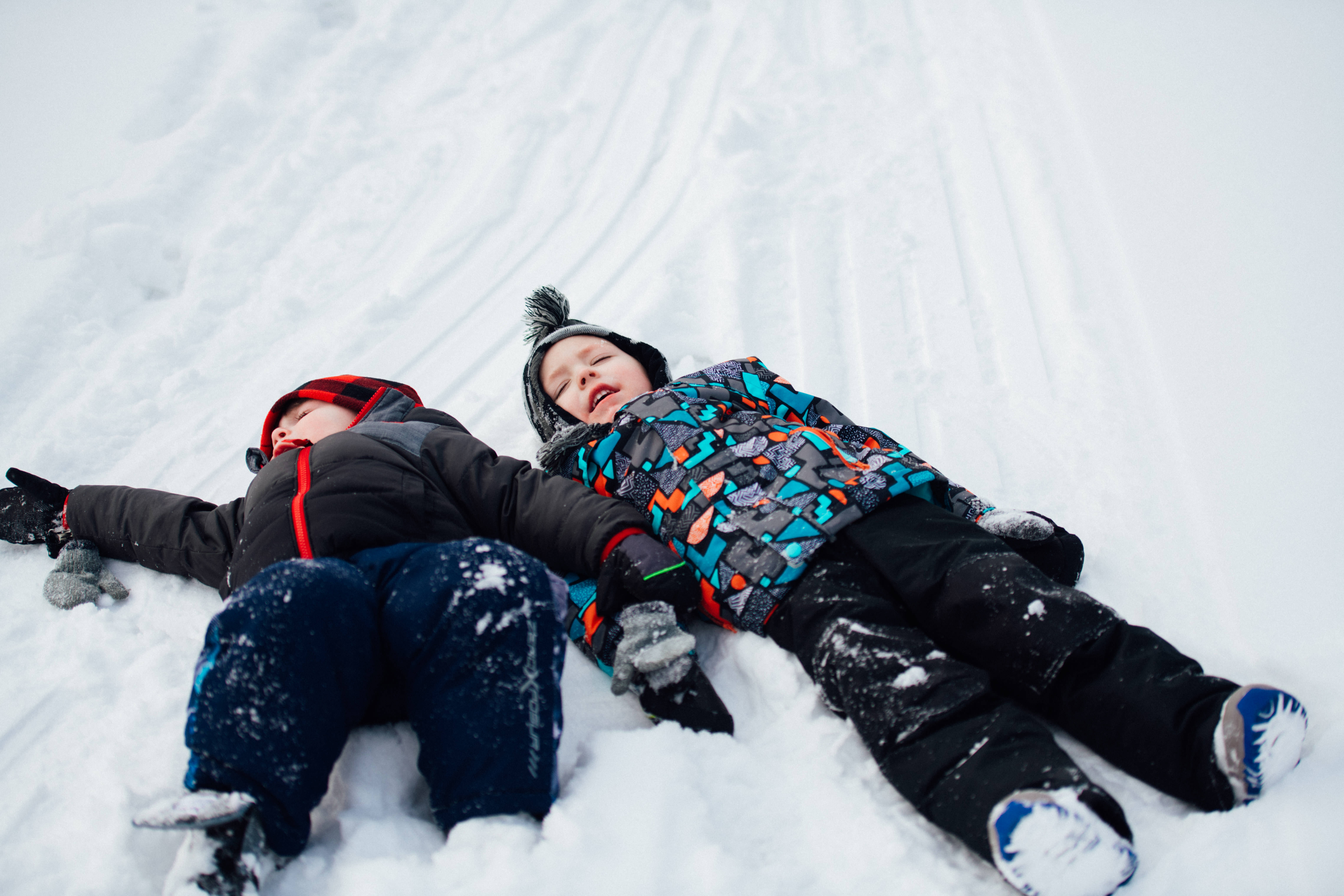 Two kids making snow angels at Little Sprouts in Waterford MI
