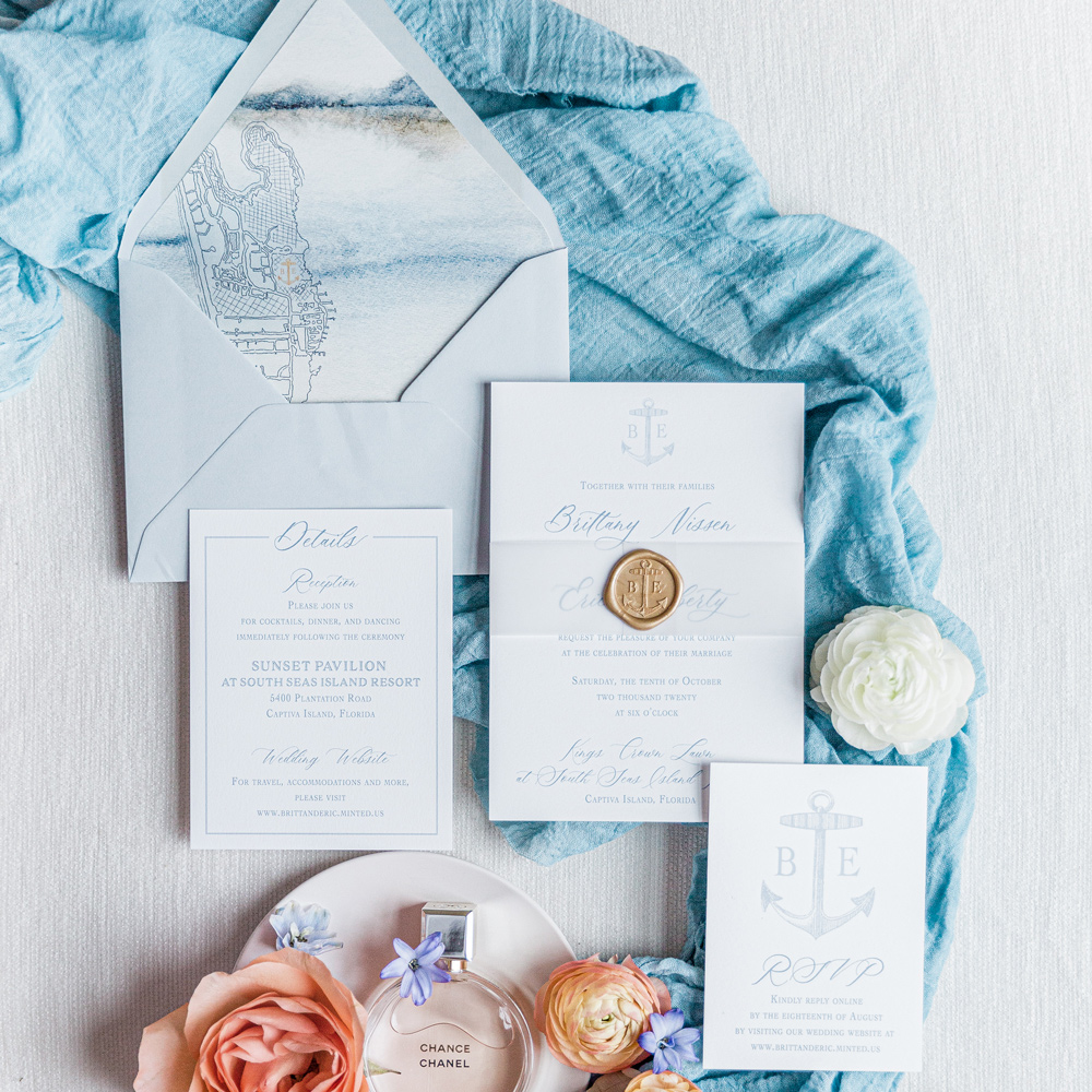 Captiva Island wedding invitation with illustration of Captiva Island Florida, wax seal, and anchor monogram in hues of dusty blue.