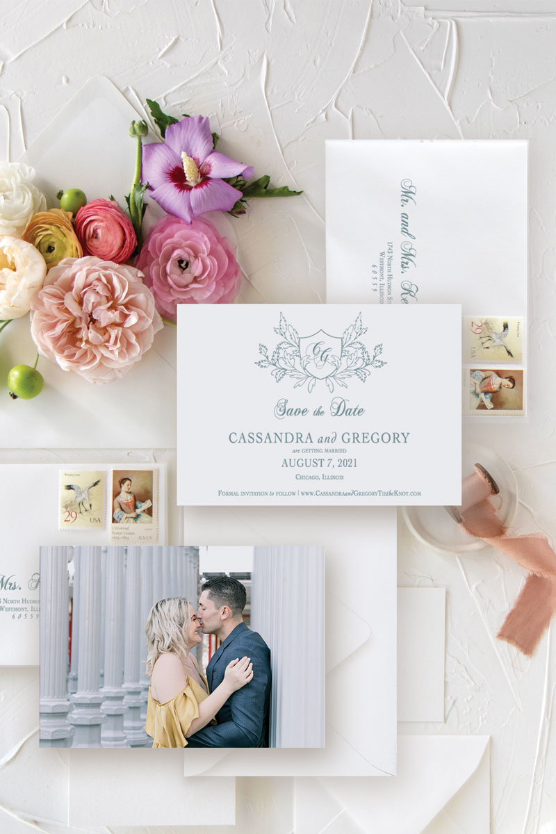 Save the date with wedding crest and engagement photo with colorful wedding flowers and dusty blue ink.