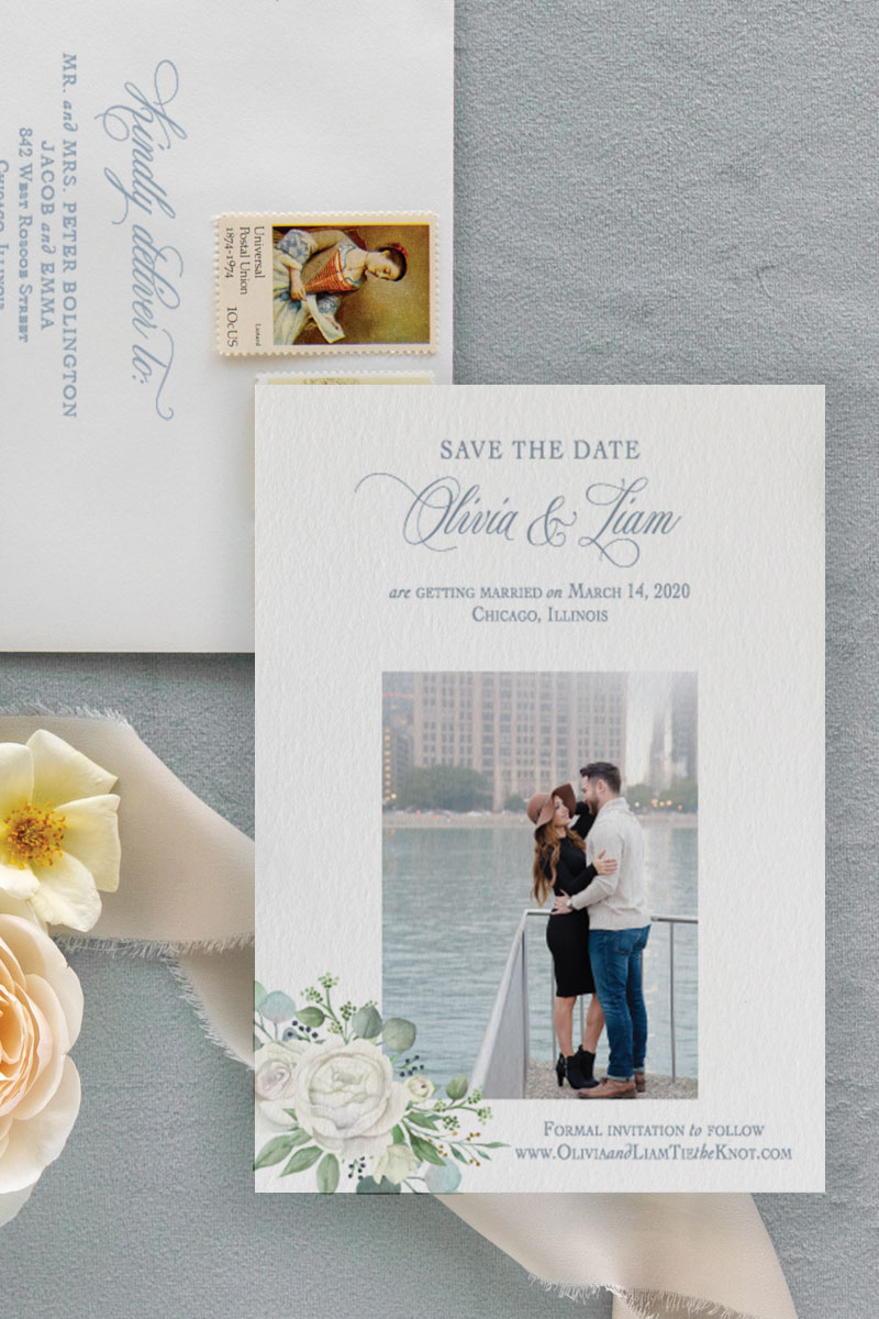 Picture save the date with watercolor eucalyptus and ivory and white roses and addressed envelopes with pretty wedding flowers.