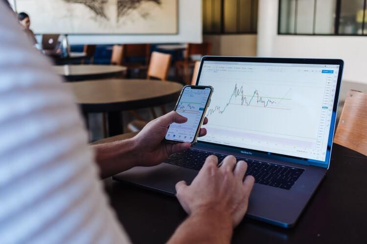 Pessoa consultando dados com um notebook e um celular.