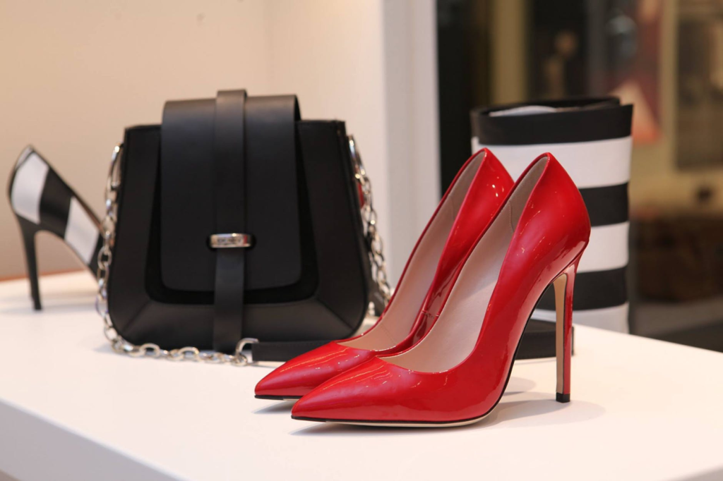 Detalhe de sapatos e bolsa femininos expostos em uma loja de calçados.