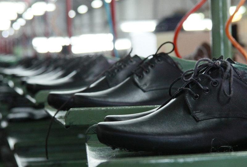 Sapatos masculinos dispostos em prateleiras de uma fábrica.