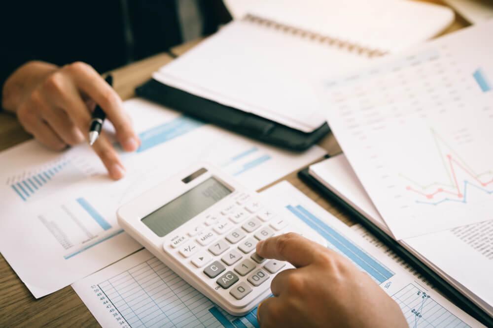 Calculadora e papeis para realizar os resultados das ações de vendas.