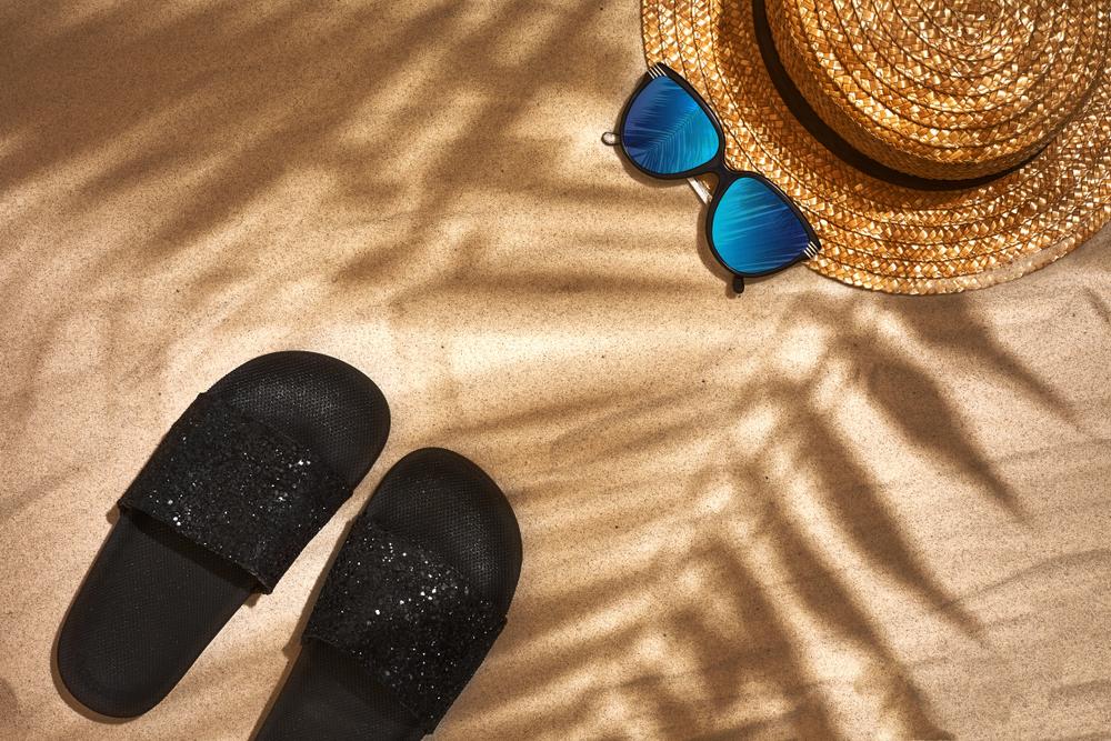 Chinelos de tira larga preto com glitter na areia da praia.