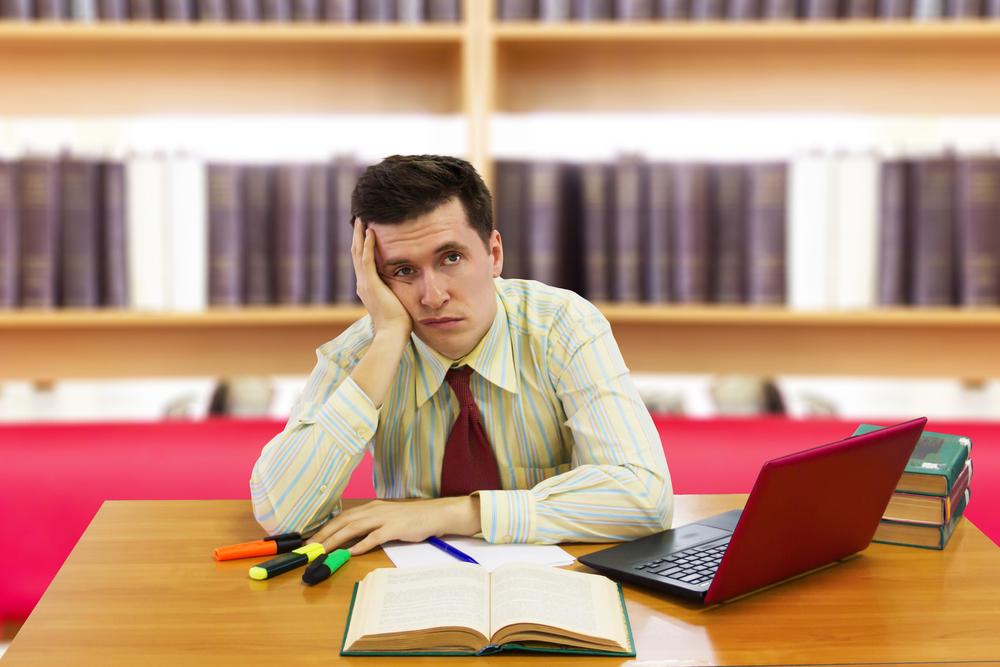 Funcionário desanimado sentado à mesa do trabalho, com um computador em sua frente.