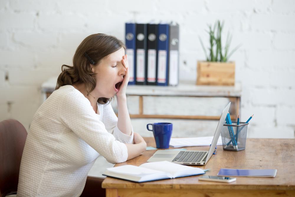 Mulher bocejando na frente do computador.