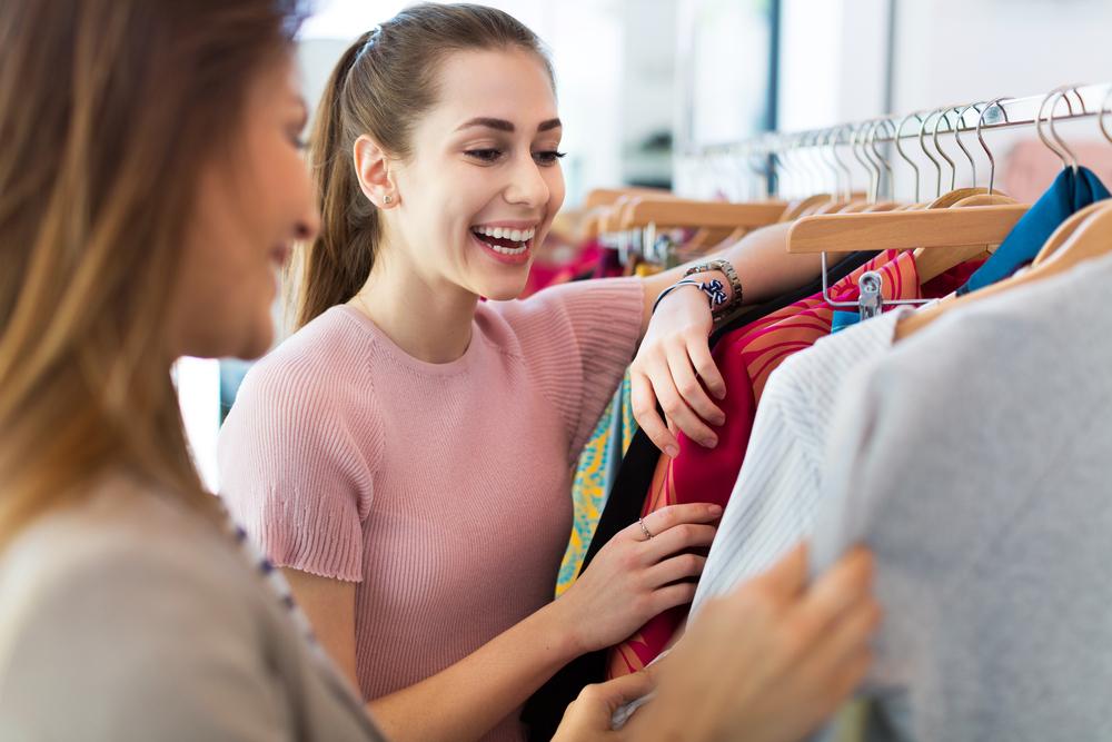 Vendedora sorrindo ao realizar a abordagem ao cliente e mostrar camisetas.