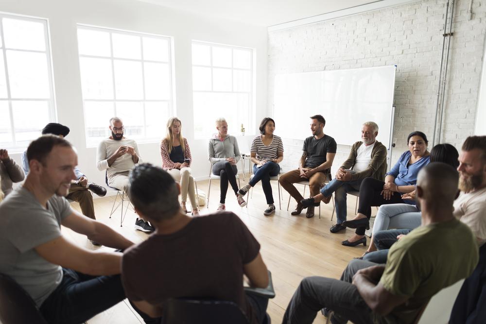 Pessoas reunidas em círculo para dinâmica de motivação.