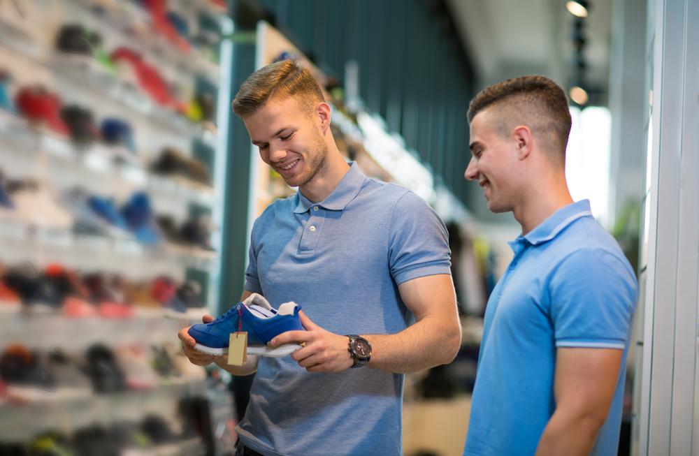 Vendedor realizando a abordagem ao cliente e mostrando tênis ao consumidor.