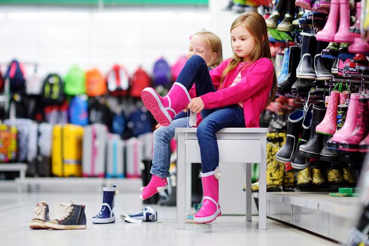 Criança provando galocha em loja que revende calçados infantis.