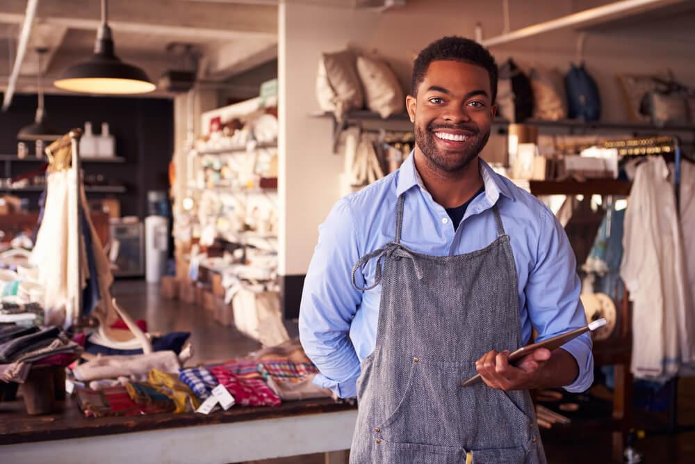 Vendedor sorrindo para o cliente, com almofadas ao fundo.
