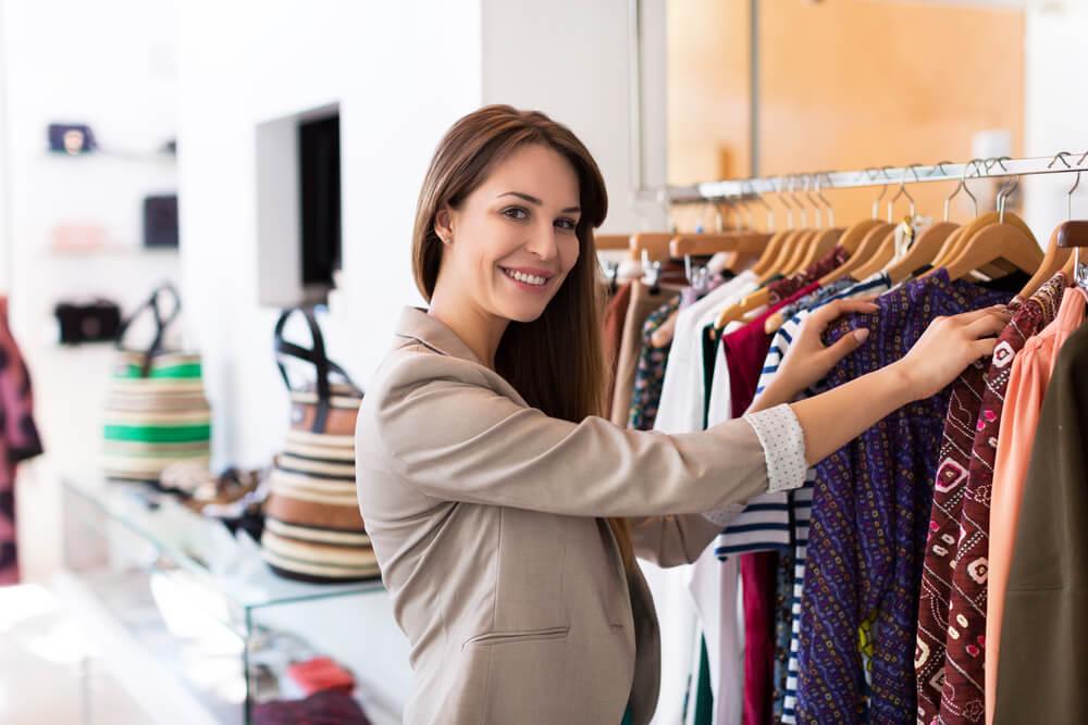 Como uma boa vendedora, a mulher está sorrindo enquanto organiza uma arara de roupas.