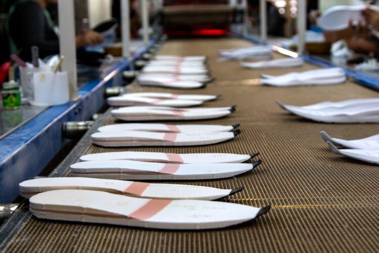 Esteira de produção com solados de calçados em EVA.