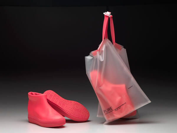Embalagem para calçados em formato de bag da Ruco feita de plástico transparente e com detalhes em rosa.