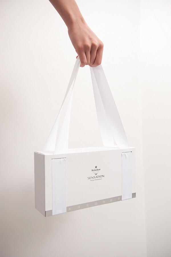 Embalagem de cerveja especial da Heineken, branca e com alças de cetim acopladas para carregar com facilidade.