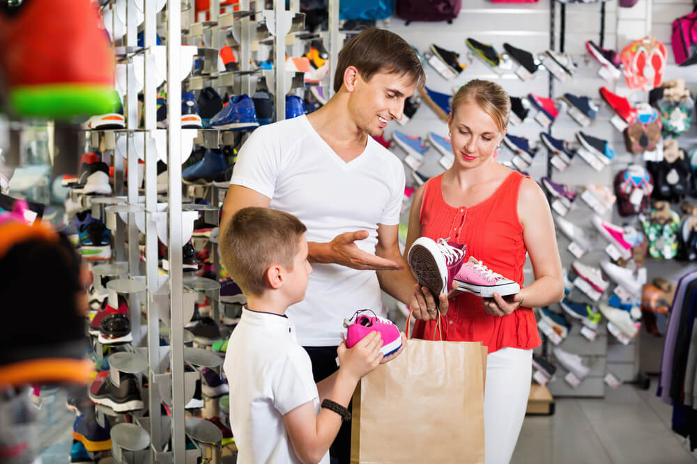 Vendedor apresentando calçados para clientes.