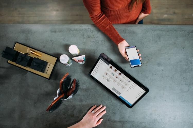 Software de gestão utilizado em um smartphone e um tablet, lado a lado.