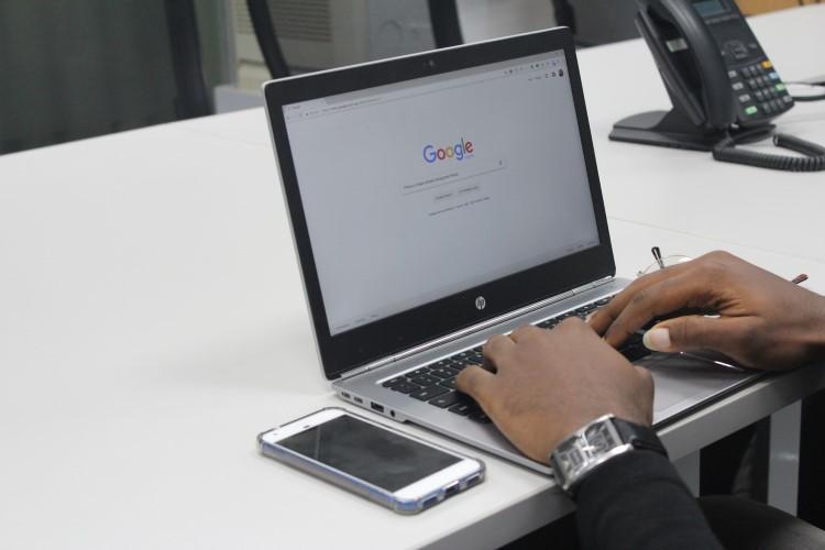 Pessoa fazendo uma busca no Google, procurando bons fornecedores de calçados no atacado.
