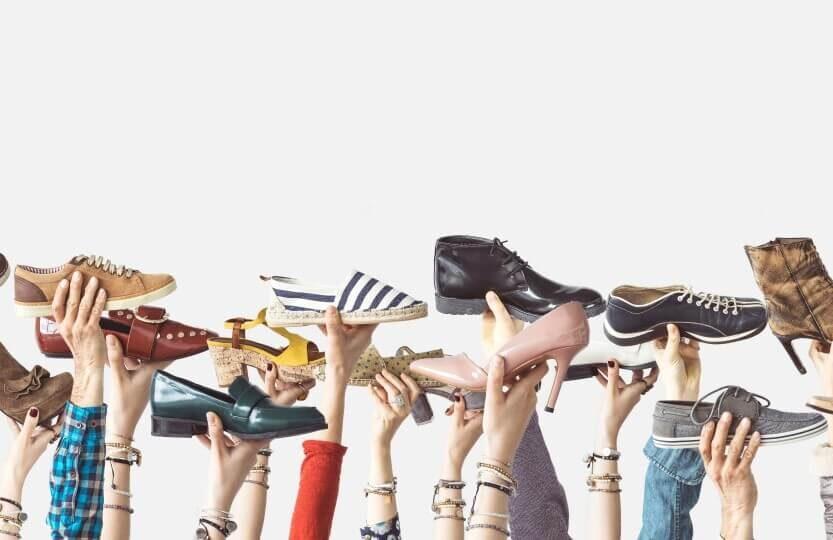 Mãos levantadas segurando calçados.