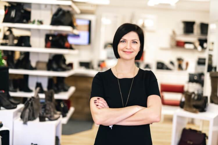 Empreendedora do varejo calçadista em sua loja.