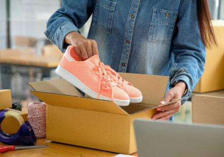 Mulher embalando calçado após descobrir como vender calçados pela internet.