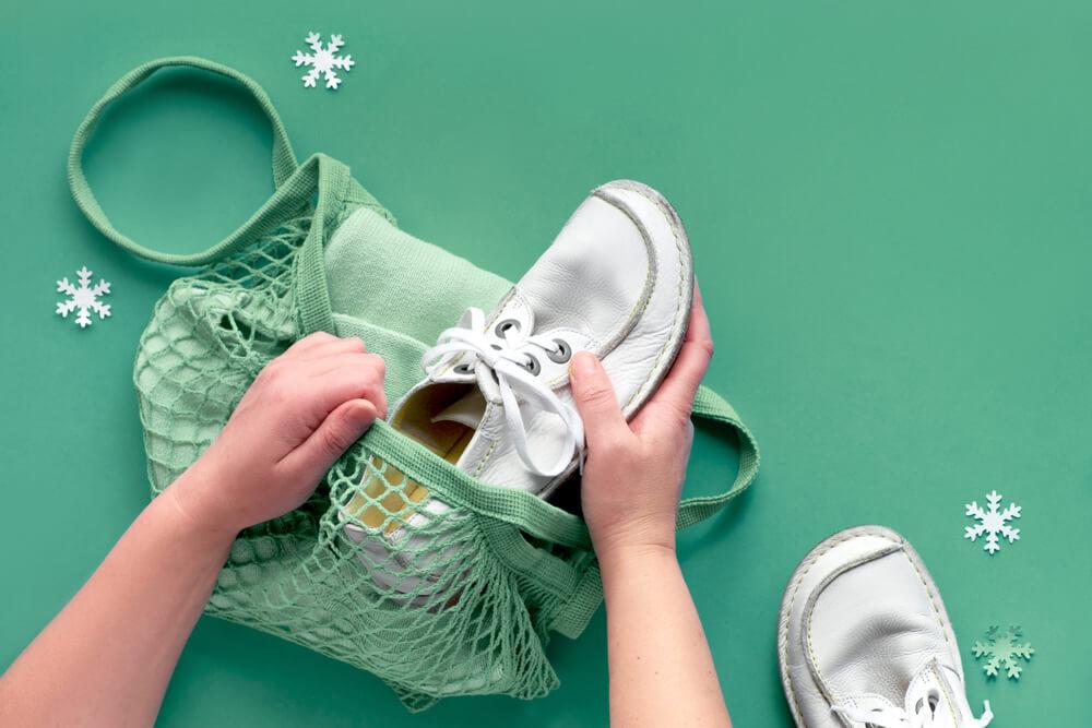 Pessoa colocando um tênis em uma sacola para armazená-lo de acordo com o consumo consciente de calçados.