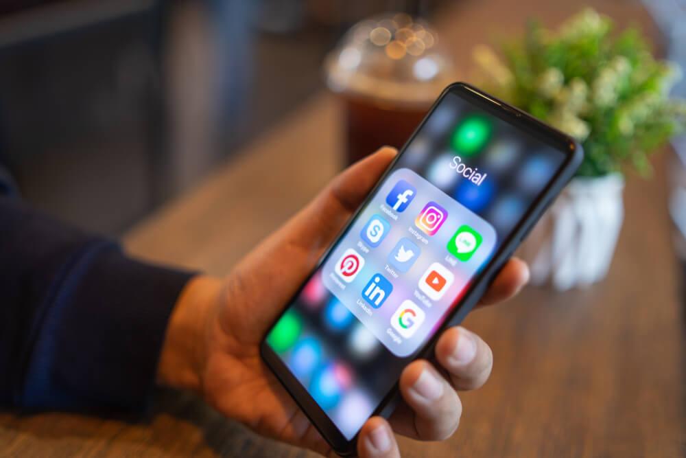Pessoa segurando celular com várias redes sociais abertas.