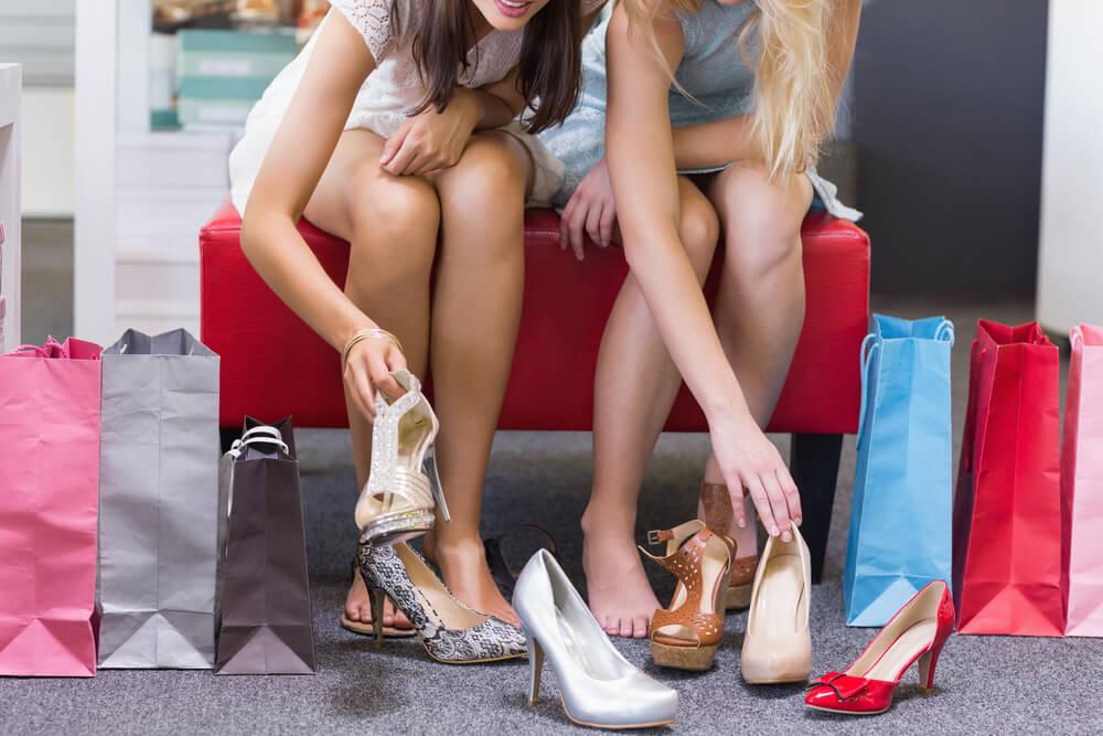Mulheres provando calçados em loja.