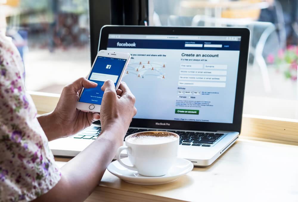 Mulher mexendo no Facebook pelo celular e pelo notebook com uma xícara de café ao lado.