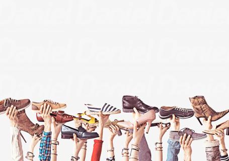 Diferentes modelos de calçados sendo segurados no ar por diversos braços levantados.