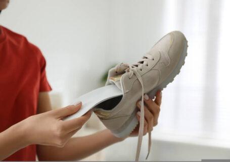 Mulher inserindo palmilha para calçados em um tênis de corrida.